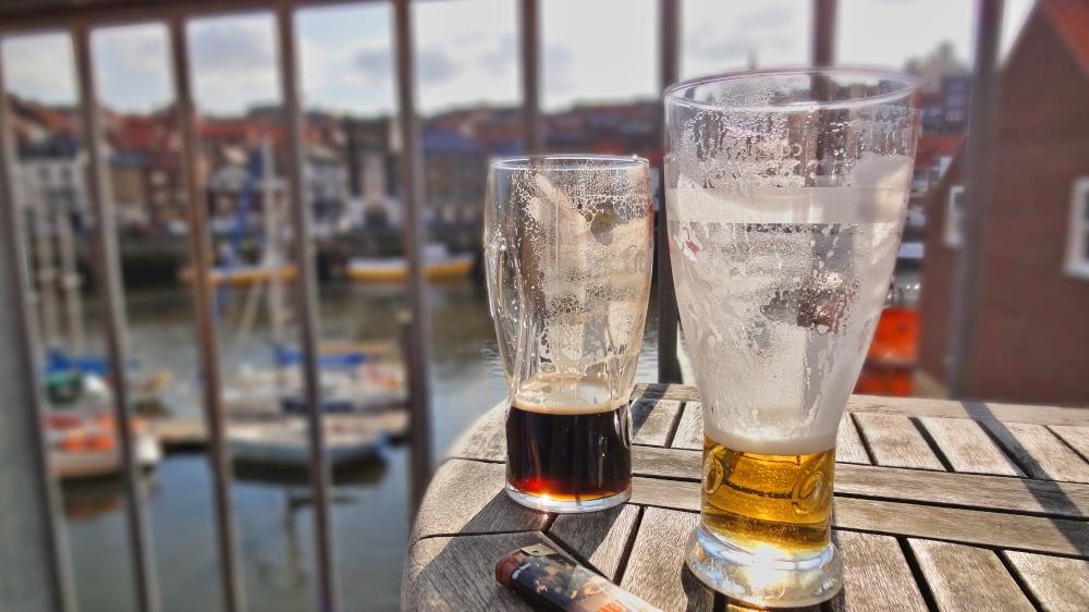 Abbildung eines Pint und half-pint zum Vergleich der Serviergroessen. Blick auf den Hafen von Whitby.